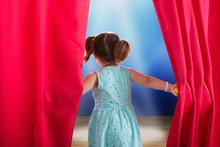 Girl Peeking Through A Stage Curtain