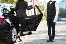 Valet Opening Door For Businesswoman Getting Out Of A Car