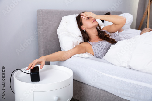Fototapety, obrazy: Woman Sleeping On Bed Turning Off Alarm Clock