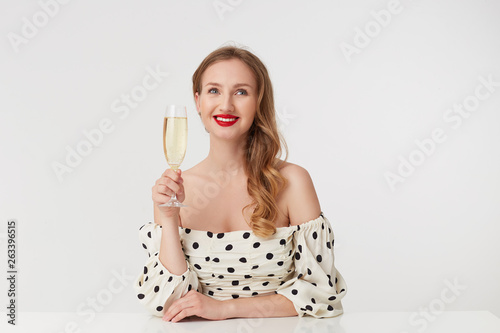 Vászonkép  Young beautiful blue-eyed girl with long blond hair, with red lips, siting at the table with a glass of champagne, playfully looks away, dreaming, smiling, isolated over white background