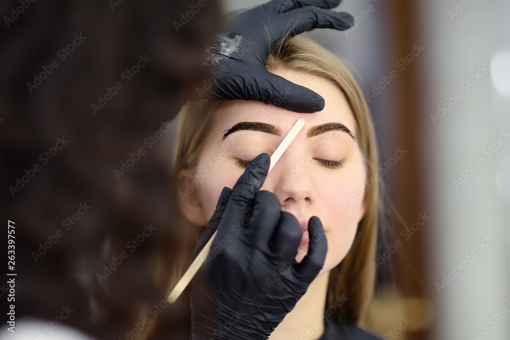 Fototapety, obrazy: Cosmetologist making eyebrows design. Attractive woman getting facial care at beauty salon. Architecture eyebrows.