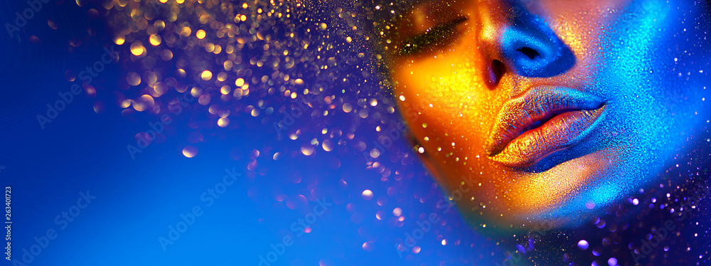 Fototapeta Fashion model woman face in bright sparkles, colorful neon lights, beautiful sexy girl lips. Trendy glowing gold skin make-up