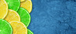 Sliced juicy lime and lemon on a concrete dark blue background. Copy space. Fresh fruits. Fruit background. Healthy food. Vitamins. Summer party. Birthday.