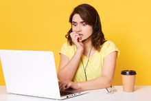 Image Of Young Attractive Female Looking At Portable Computer And Watching Horror Film, Afraid Of Something, Bites Her Nails, Full Of Fear, Studio Shot, Yellow Background. People And Emotions Concept.