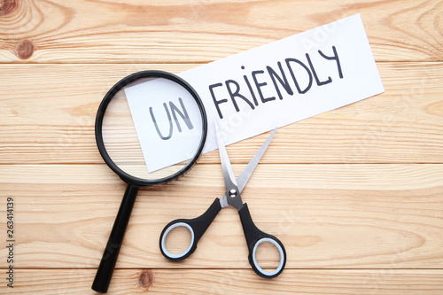 Paper with word Unfriendly, scissors and magnifying glass on wooden table Fototapet