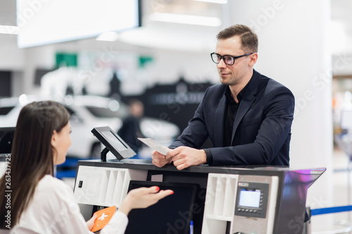 Handsome businessman handing over air ticket at airline check in counter Canvas Print