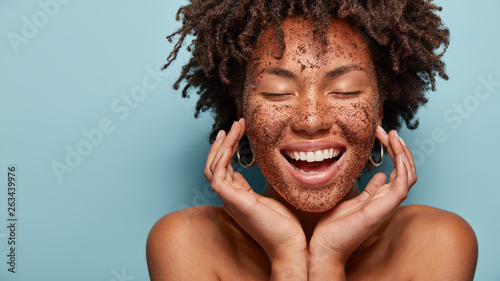 Cheerful dark skinned lady applies coffee scrub on face, pampers skin, closes eyes from pleasure, smiles positively has bare shoulders, stands against blue background, free space aside. Beauty concept - 263439976