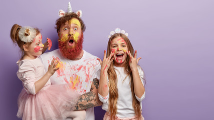Horizontal shot of shocked dad has yellow face painted with watercolors, two children have fun with father, joyful expressions, isolated over purple background with free space for promotion.