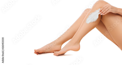Photographie woman touching with feather to her shiny smooth skin on legs after hair removed