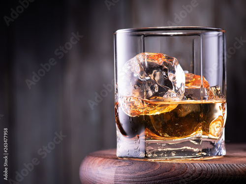 Poster de jardin Bar Glass of whiskey with ice cubes on the wooden table with wooden background