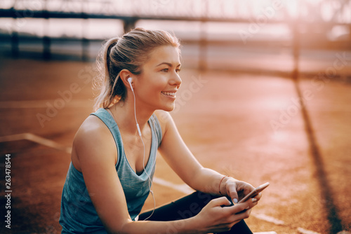 Fotografie, Tablou  Cute smiling Caucasian blonde sporty woman sitting on the court with earphones in ears and using smart phone