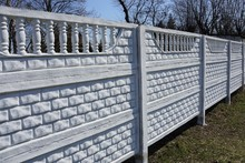 Long White Concrete Fence Outside In Green Grass