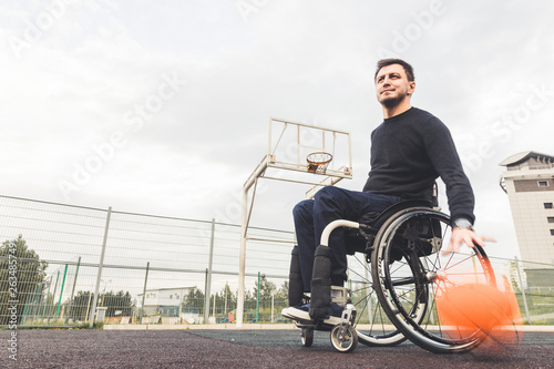Valokuva  Young man in a wheelchair playing basketball.