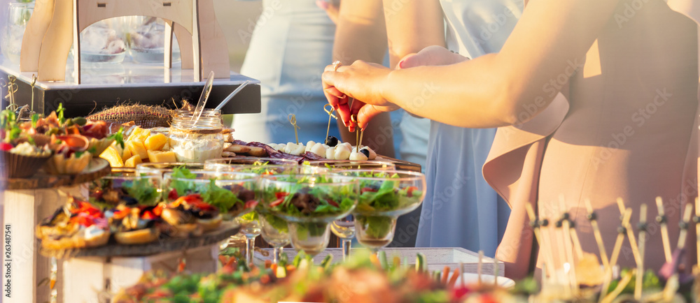 Fototapeta Beautifully decorated catering banquet table with different food snacks and appetizers with sandwich, caviar, fresh fruits on corporate christmas birthday party event or wedding celebration