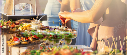 Fototapeta Beautifully decorated catering banquet table with different food snacks and appetizers with sandwich, caviar, fresh fruits on corporate christmas birthday party event or wedding celebration obraz
