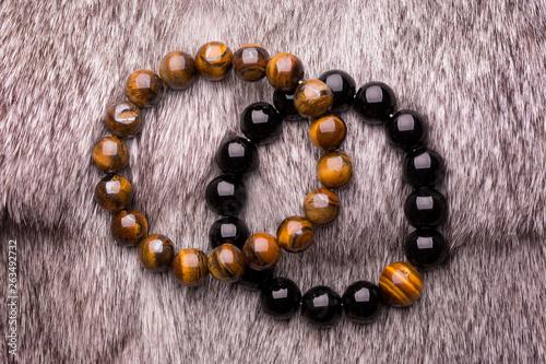 A beautiful bracelet of black stones lying on gray fur Fototapete