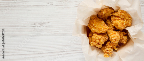 Fototapeta Fried chicken bites in paper box over white wooden background, top view. Flat lay, overhead, from above. Copy space. obraz