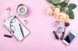 Workplace mockup with notebook, glasses, roses, phone and accessories on pink background top view. Flat lay with coffee copy space. Feminine working style concept.