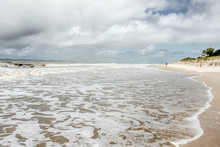 Woman Walks Along Beach At High Tide Under Stormy Sky With Turbulent Ocean