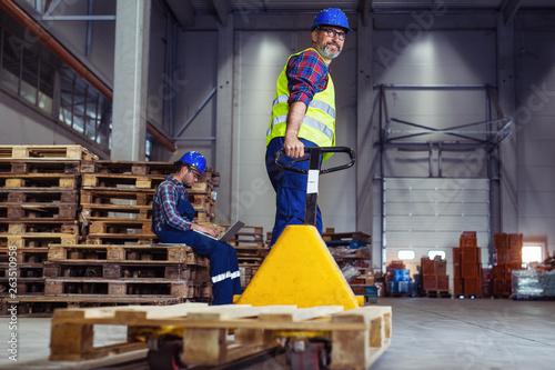 Obraz na płótnie Male warehouse worker pulling a pallet truck
