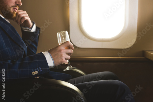 Fototapeta A young successful businessman in an expensive suit sits in the chair of a private jet with a glass of champagne in his hand and looks out the window obraz