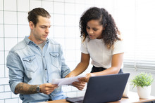 Young Mixed Race Couple Managing Their Family Budget, Going Through Receipts And Paperwork And Paying The Mortgage And Bills At Home Office
