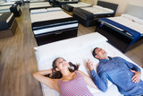 Family couple choosing mattress  in  furniture store