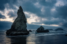 Wizard Hat Sea Stack At Famous Bandon Beach On The Central West Coast Of Oregon. Seagulls Perch The Rugged Rocks As The Ocean Sea Waves Wash Over The Rugged Rock Formation At Sunset In Summer