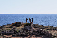 Three Humans Standing On Sea Shore In Tombs Of Kings Paphos, Cyprus. Friends Enjoy View On Sea And Talking To Each Other. Silhouettes On The Edge Of Hill. They Taking Photos The Cypriot Nature And Sea