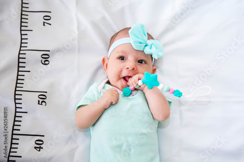 Obraz A three month baby in mint green clothes lying on a bed on which a measuring ruler for growth is drawn. Teething tool in hands, chewing - fototapety do salonu