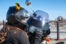 Biker Girl In Helmet With Mask Clenches Fist While Sitting In Front Of Plastic Front Cowl With Headlight Of Her Motorcycle