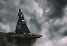 Outdoors Portrait Of A Victorian Lady In Black Standing On The Cliff.