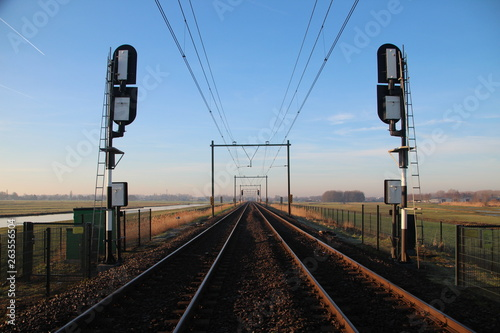 Cuadros en Lienzo Railroad double track in Moordrecht during sunrise with signals in the low polde