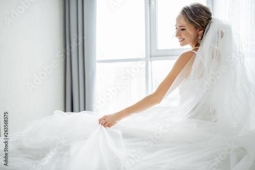 Obraz na plátne Amazing young bride posing in a beautiful wedding dress with wedding veil near w
