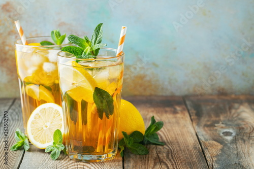 Traditional iced tea with lemon and ice in tall glasses on a wooden rustic table Canvas Print