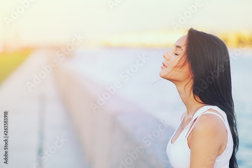 Fototapeta Side view profile portrait of a happy brunette woman relaxing breathing fresh air outdoors in summer Girl close eyes doing deep breath exercises. Positive emotion success, peace of mind, zen concept. obraz