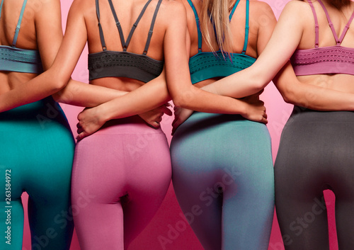 Stampa su Tela Group of four women buttocks in blue gray and brown sport wear standing together