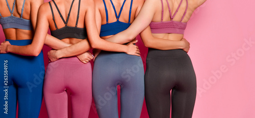 Group of four women buttocks in blue gray and brown sport wear standing together Canvas-taulu