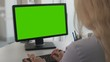 Female office worker typing documents on personal computer with green screen