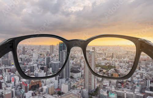 Fotografie, Obraz  Looking through eyeglasses to city sunset view, focused on lens with blurry back