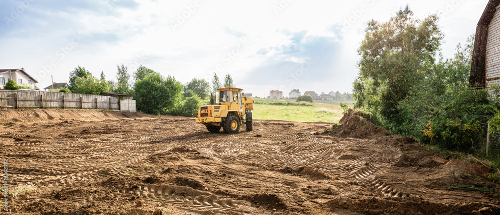 large yellow wheel loader aligns a piece of land for a new building, wih copy space, banner
