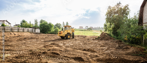 Obraz na plátně large yellow wheel loader aligns a piece of land for a new building, wih copy sp