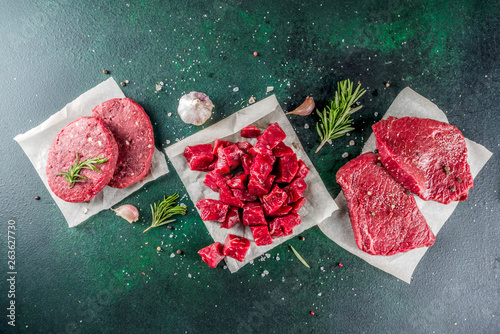Various raw beef meat with spices and herbs, dark concrete background copy space