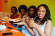 Four young african girls in bright colored restaurant with pizza slices on plate and juices.