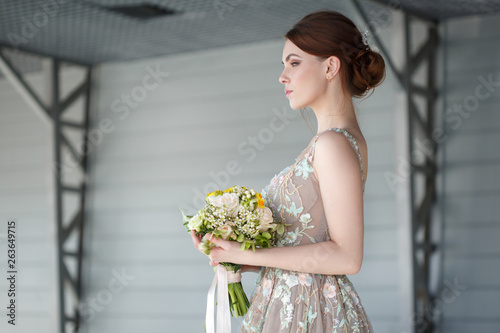 Fotografía  Portrait of an elegant bride in an unusual chic dress with a bouquet in her hands