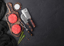 Fresh Raw Minced Homemade Farmers Grill Beef Burgers On Vintage Chopping Board With Spices And Herbs And Meat Hatchet, Fork And Knife On Black Board. Space For Text