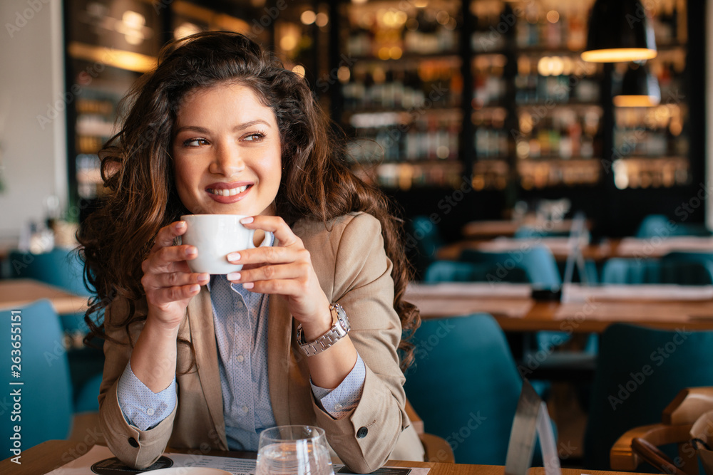 Fototapeta Young woman is drinking coffee in a cafe