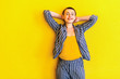 canvas print picture - Portrait of happy young short hair beautiful woman in yellow shirt and striped suit standing, holding her head and looking at camera with toothy smile. indoor studio shot isolated on yellow background