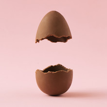 Chocolate Easter Egg Broken In Half On Pastel Pink Background With Creative Copy Space. Minimal Easter Holiday Concept.