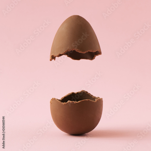 Chocolate Easter egg broken in half on pastel pink background with creative copy space Fototapete